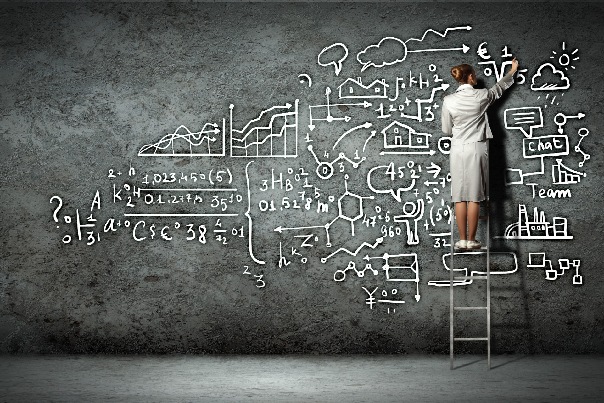 Business woman writes out commission formulas on chalk board.