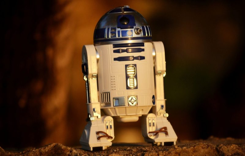 An R2 Unit from Star Wars stands in front of a rock face.