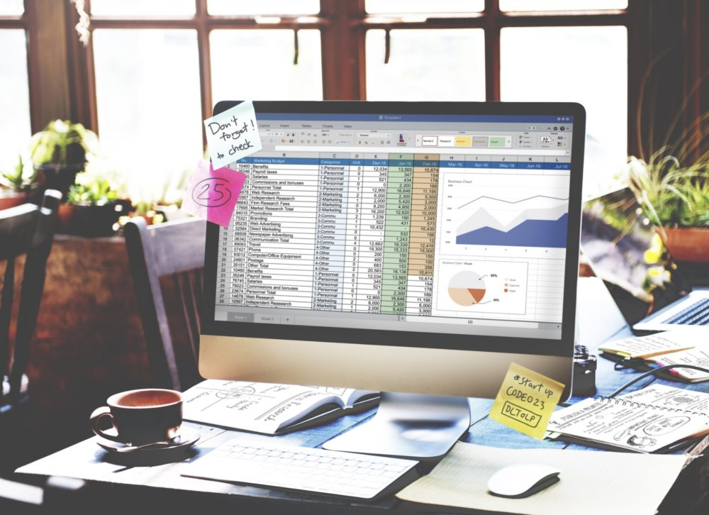 Spreadsheet used for sales commission calculations displayed on a computer screen with sticky notes for reminders.