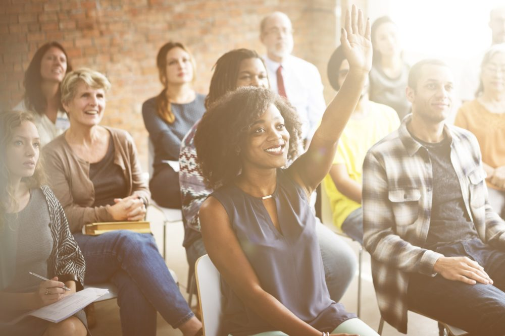 Woman sits with a group of salespeople and raises her hand because she knows about sales commission management.