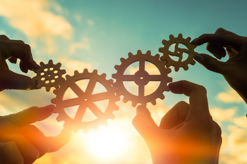 Hands hold gears that fit together the same way that Core Commissions can make sales commission management a piece of your overall business systems.