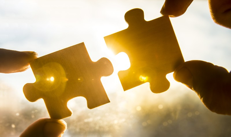 Two puzzle pieces come together.