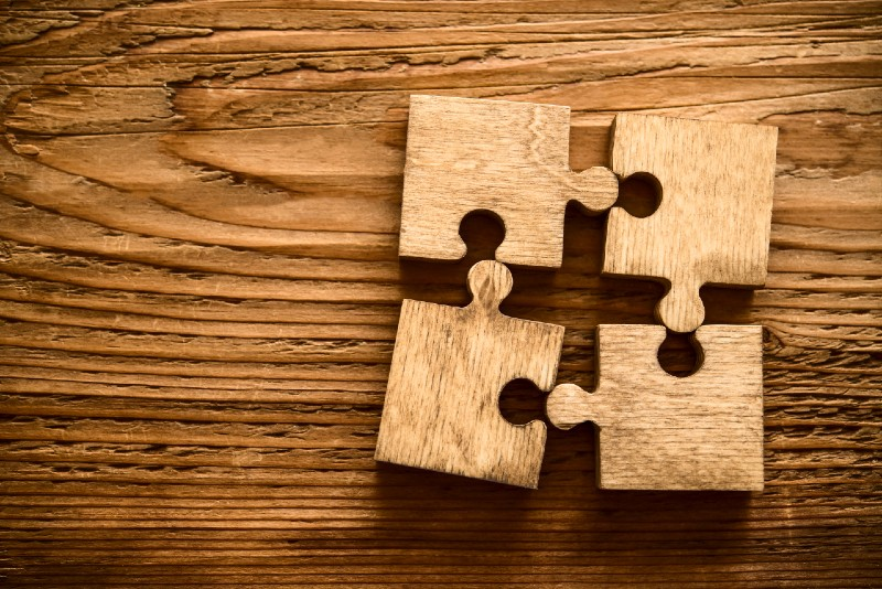 A four-piece wooden puzzle on a wood table top represents how sales commission management fits into payroll services.