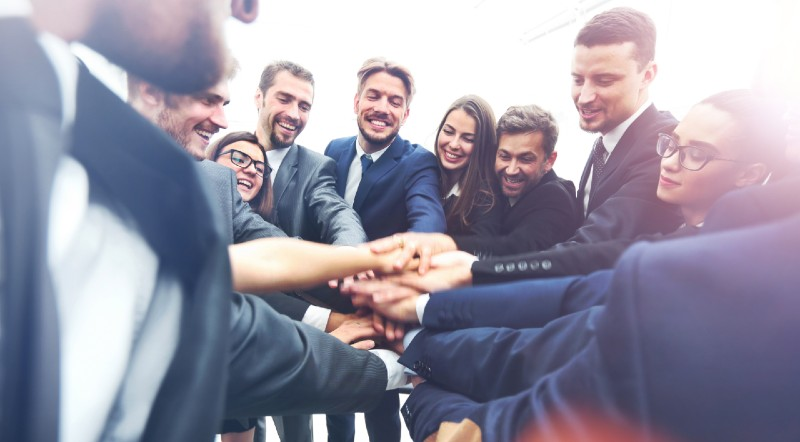 Salespeople dressed in suits throw their hands in for a cheer to express teamwork.