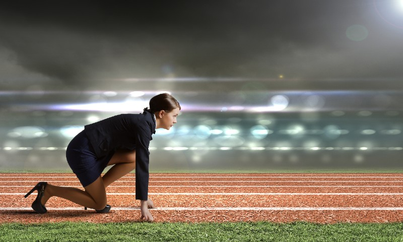 Sales woman prepares at starting line where she'll set off to reach her sales quota.