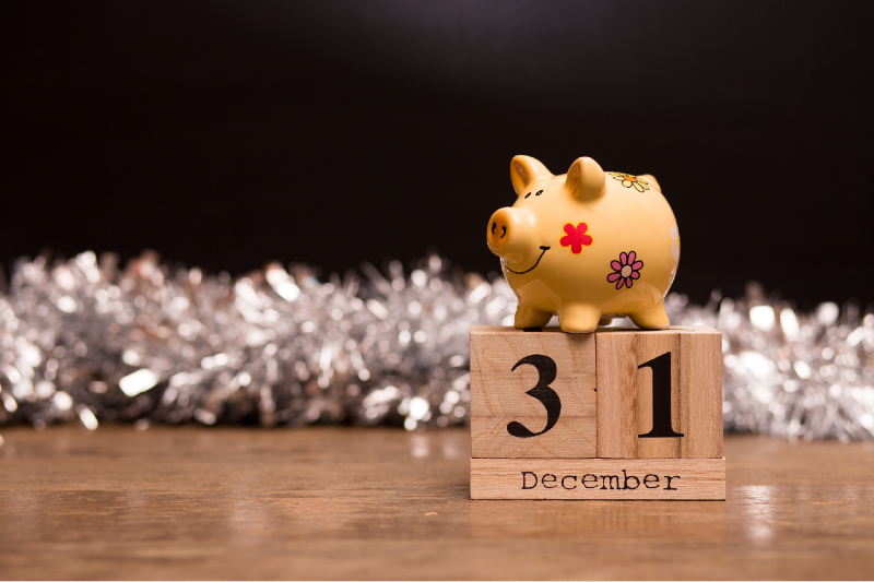 A piggy bank stands atop wooden squares that depict December 31 to represent year-end bonuses.