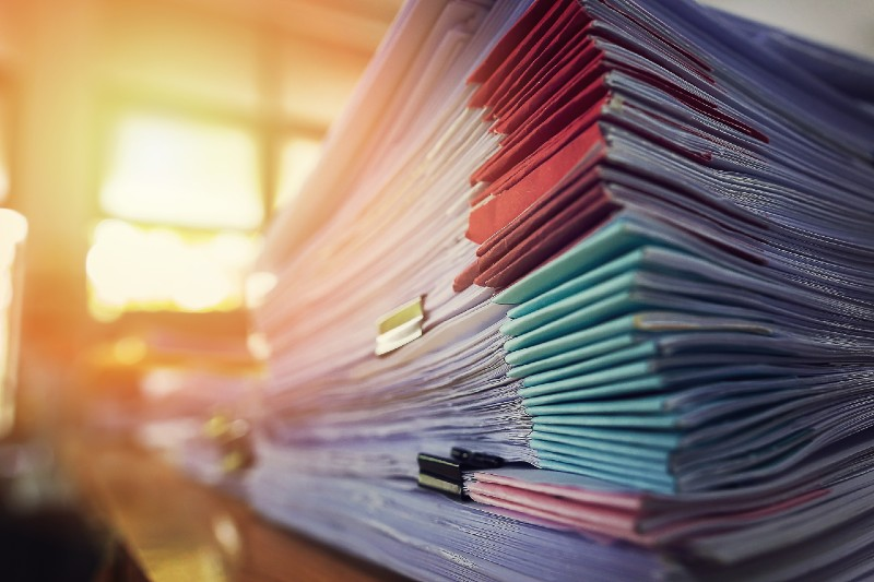 Piles of documents, like insurance commission statements, are piled on an administrator's desk.