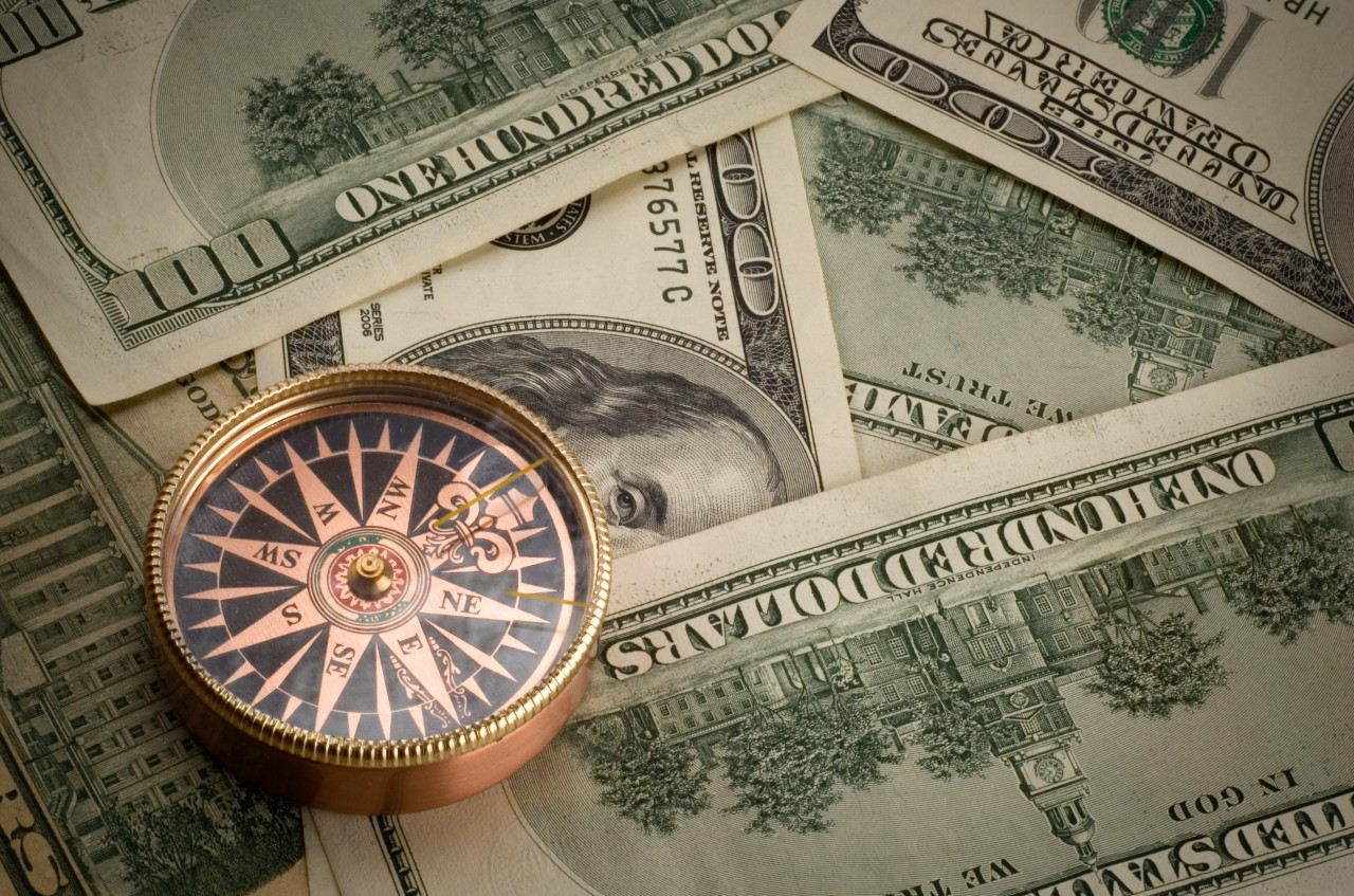 Gold compass sits atop a stack of cash representing how sales commission data can lead sales representatives and agents toward success.