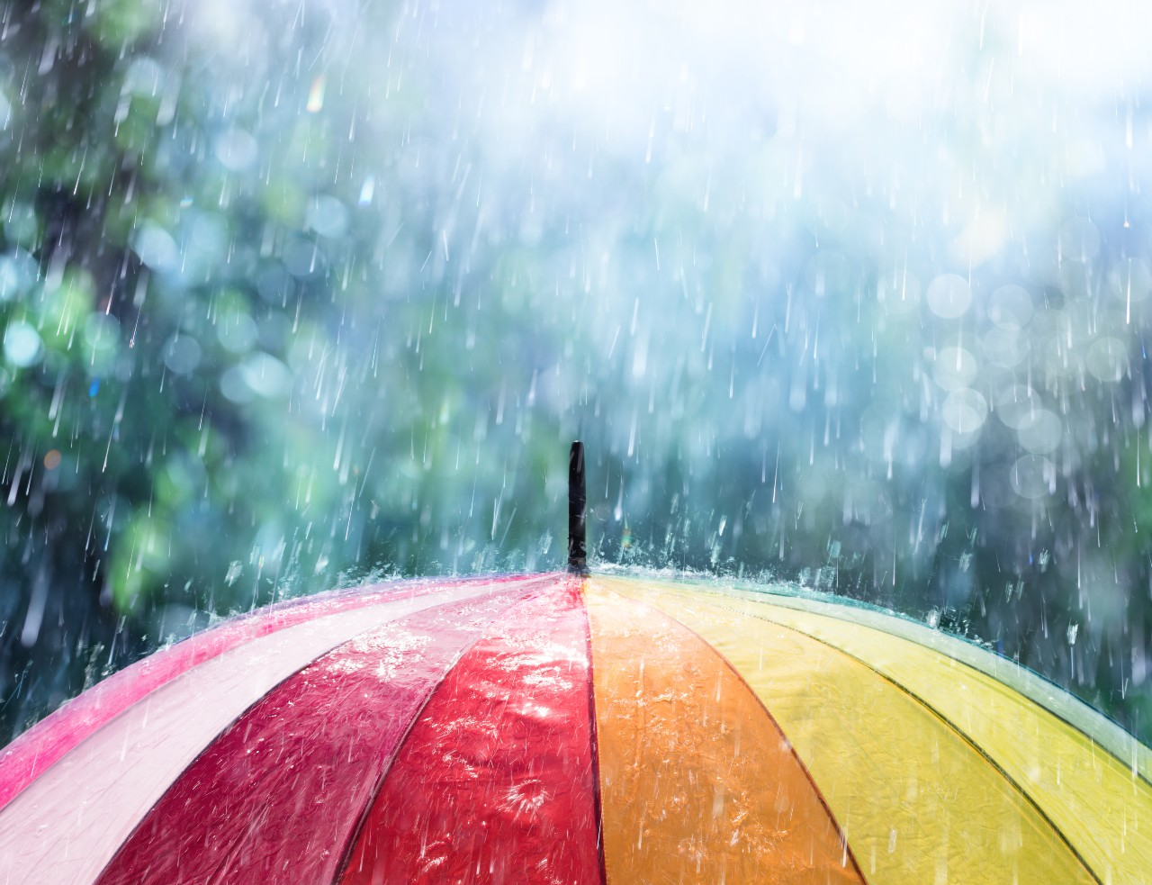 Colorful umbrella protects from a rainstorm like insurance policies protect clients.