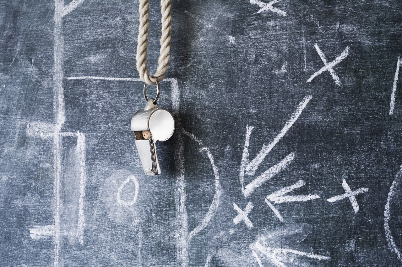A coach's whistle hangs over a chalkboard to represent how commission management teams need to be coached and trained.