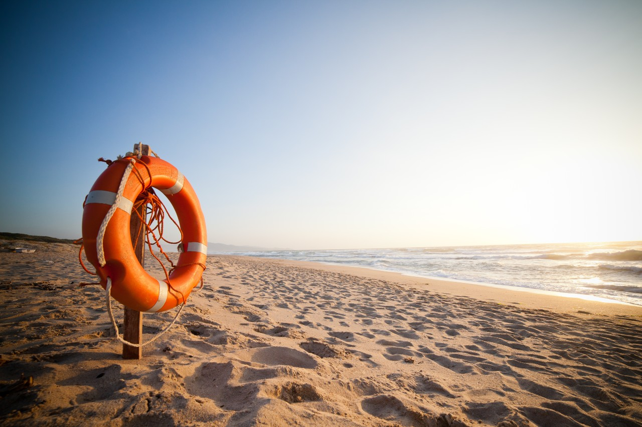 Life raft hangs on rack on beach representing life insurance sold by independent agens.