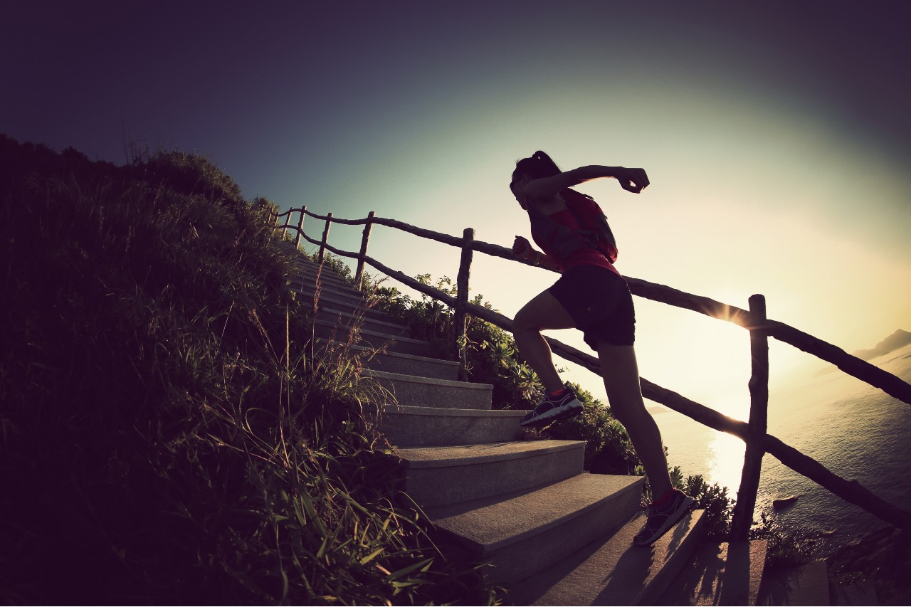 Woman runs up steps toward the top of a hill like salespeople going up steps toward a sale.