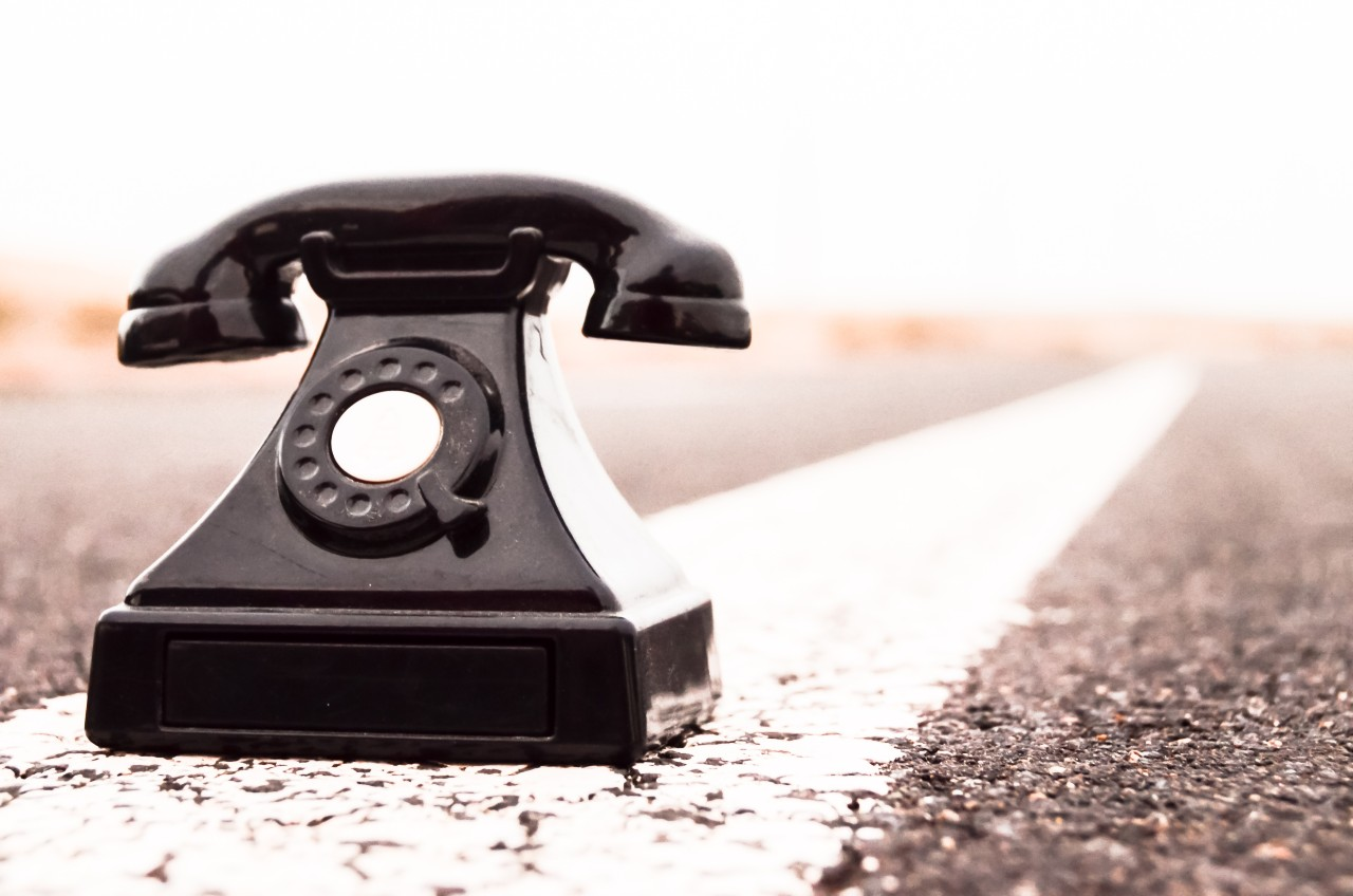 A telephone sits on the center line of a paved road representing the direction prospecting can take with proper sales incentives.