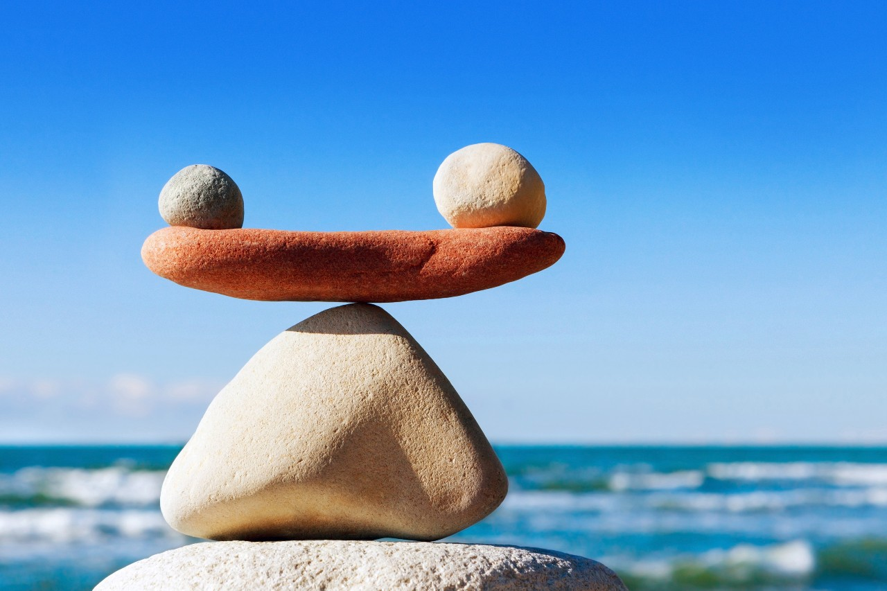 Two rocks balance on a third rock much the way sales organizations need to balance commission draws against quota.
