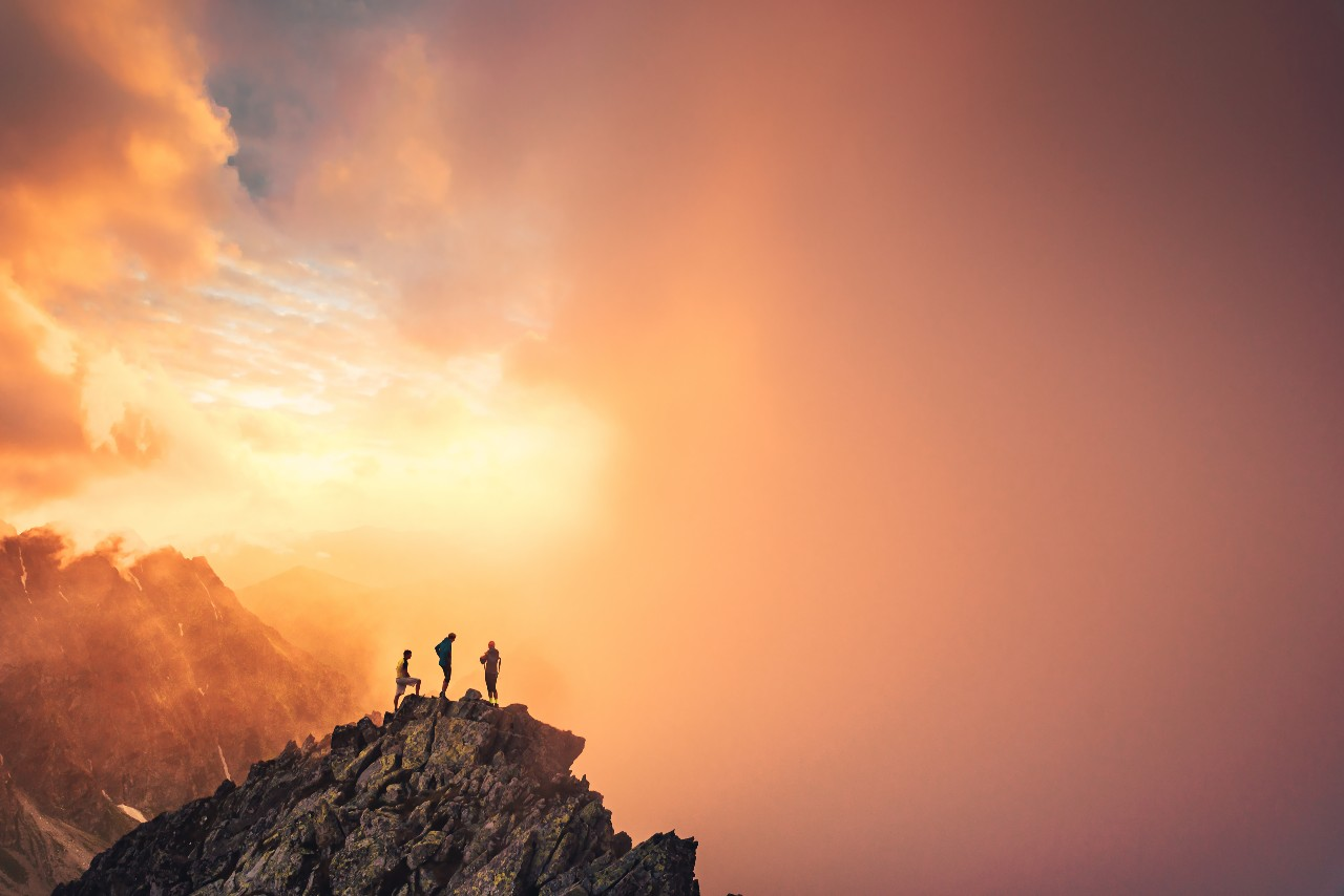 Three people stand on a summit with a sunset in the background representing employees reaching their goals