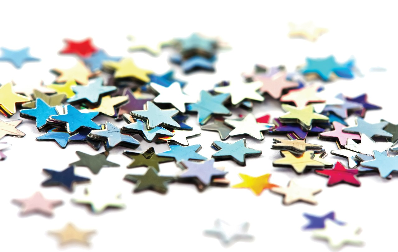 Individual star stickers scattered on a white surface represent how distinct and unique each Core Commissions Managed Services client is.