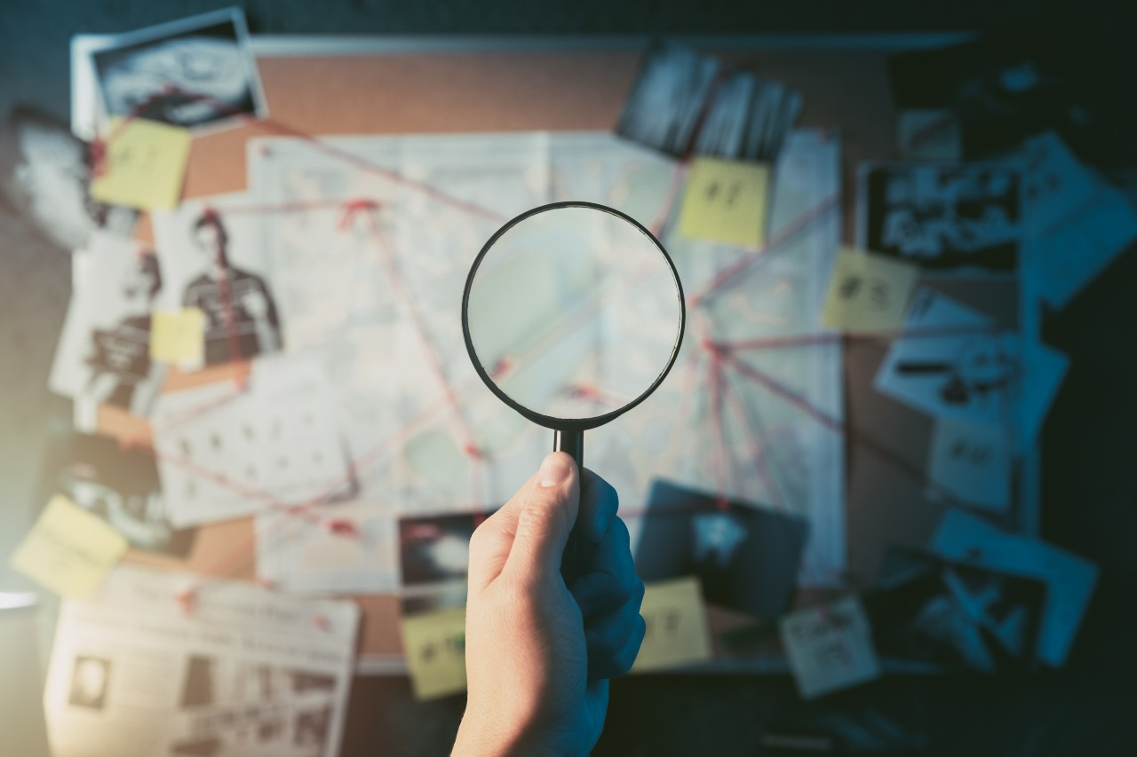 Hand holds magnifying glass in front of evidence board searching for answers about sales commissions.